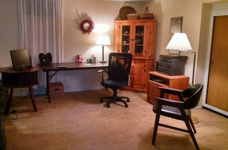 LL Guest Suite sitting area with Wi-Fi, large desk,  microwave, mini-fridge, and tv.