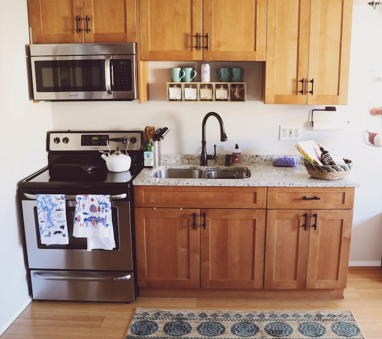 The kitchen has stainless steel appliances, granite countertops, a double sink, full refrigerator and freezer, and all the essentials for cooking, baking, tea and coffee