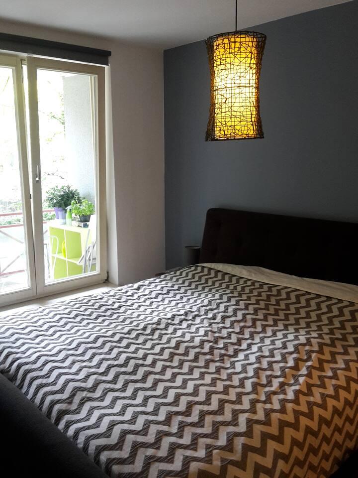 Schlafzimmer mit Boxspringbett (1,80 cm breit) Verdunkelungsrollo und Blick ins Grüne