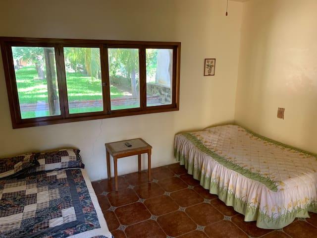 recámara en planta baja con dos camas y al frente con una terraza