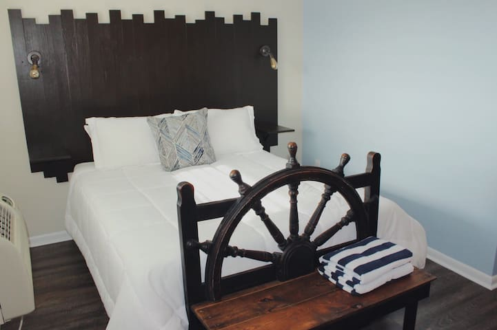 Our queen-sized memory foam mattress is framed by a unique headboard and Captain's wheel entry bench. Beach towels provided!