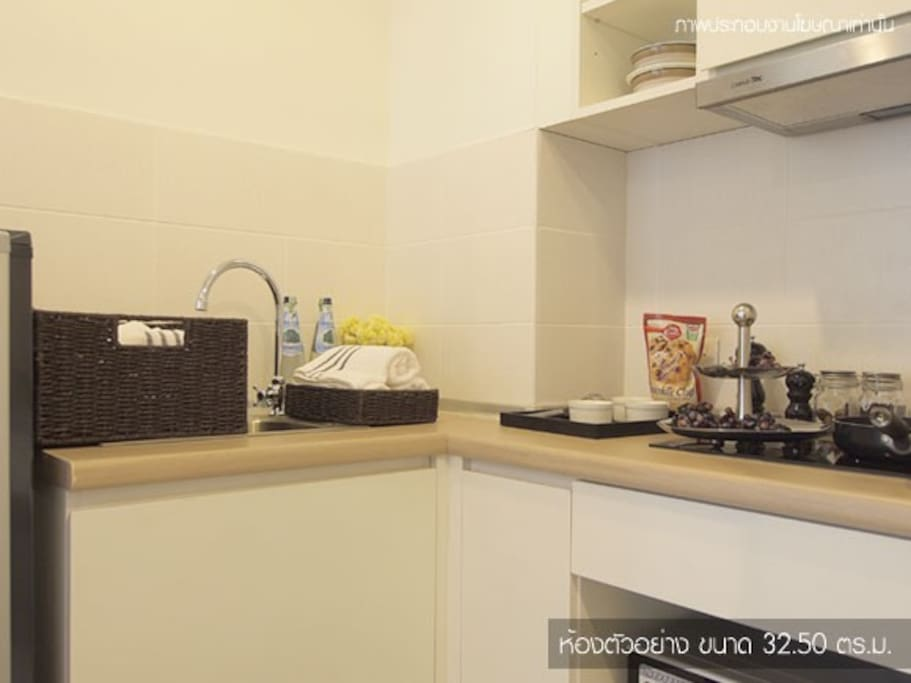 A little kitchen is ready for cooking. The kitchen has microwave, stove, refrigerator, rice cooker and a boiler.