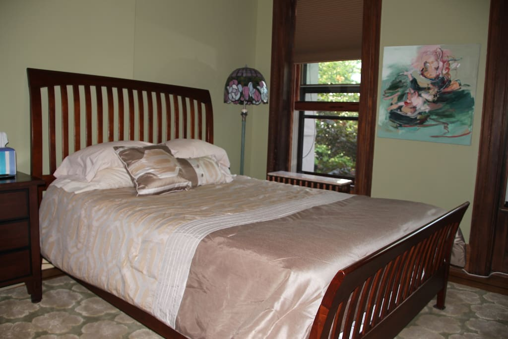 Your queen-sized bed, brand new, with Tiffany lamp behind and exquisite rug.