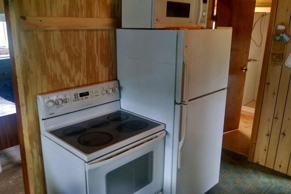 Newer Fridge, Stove, and Microwave within the full kitchen.