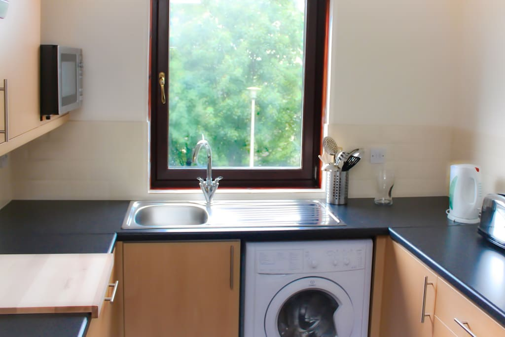 Modern kitchen with washer/dryer, oven, hob, dishwasher and microwave.