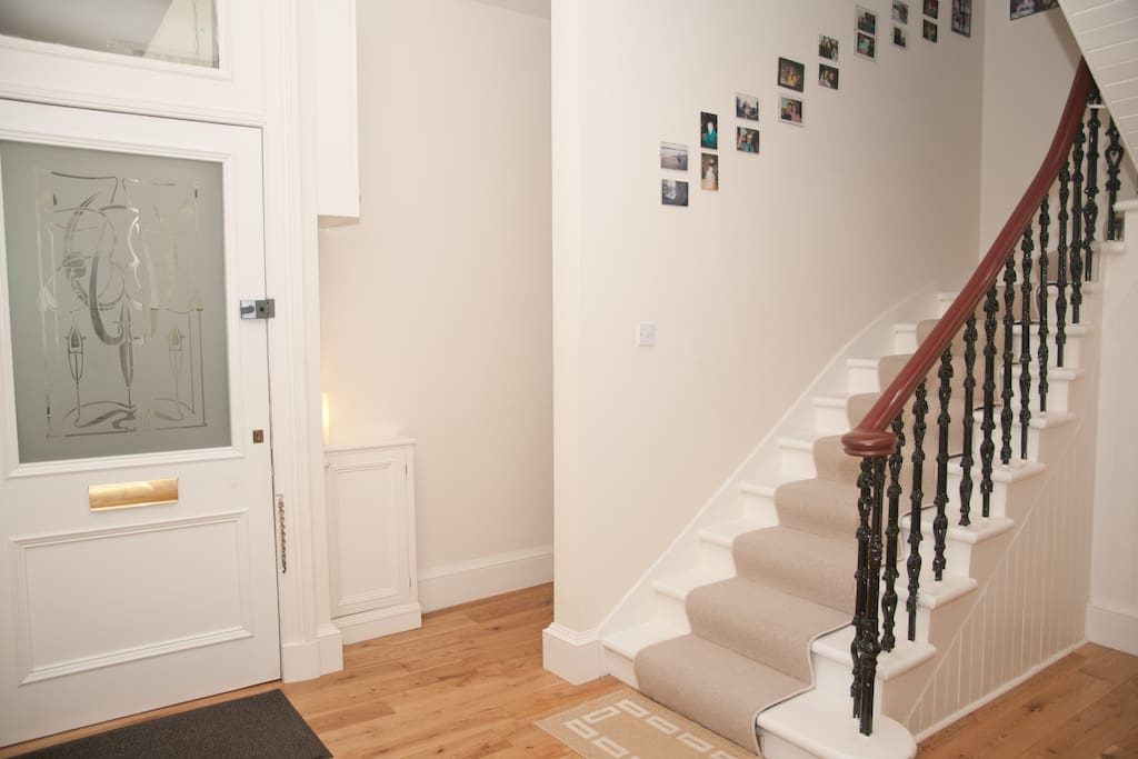Hall with stairs up to upper level and front entrance door