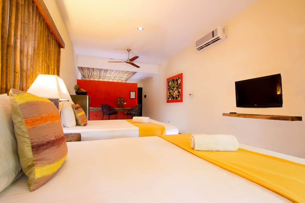 2 Double beds with sitting area in the background.