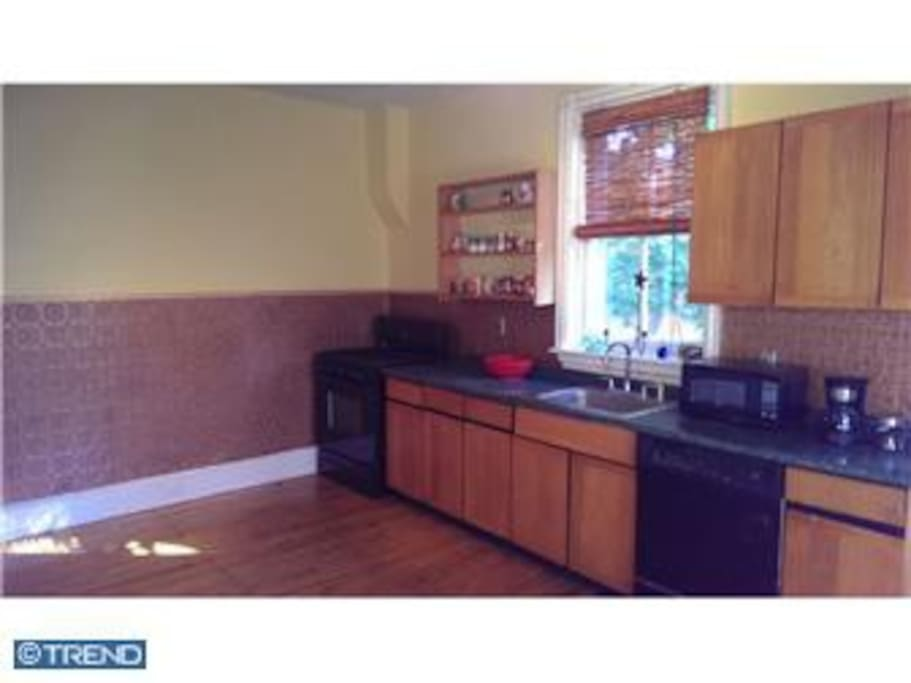 Large eat in kitchen adjoins great room with TV . Gas stove , large refrigerator,  dishes, stocked pantry