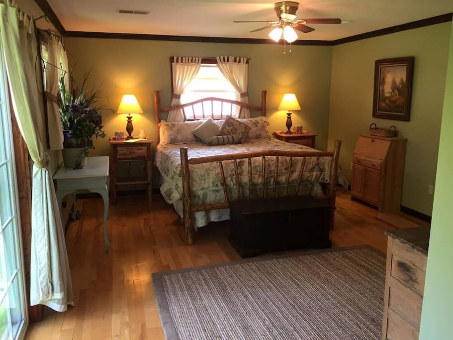 King sized log bed in spacious room overlooking stocked pond & pasture.