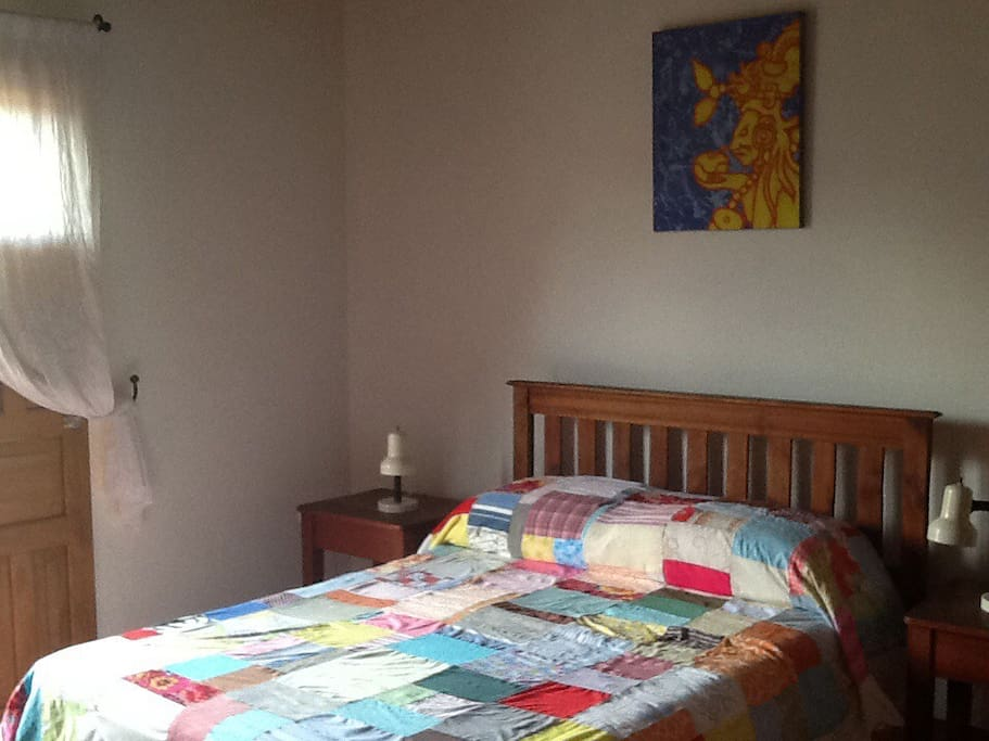 Sturdy artisan crafted hardwood full bed w/ firm mattress & patchwork quilt.