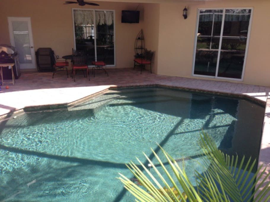 Pool in backyard screened in with patio set