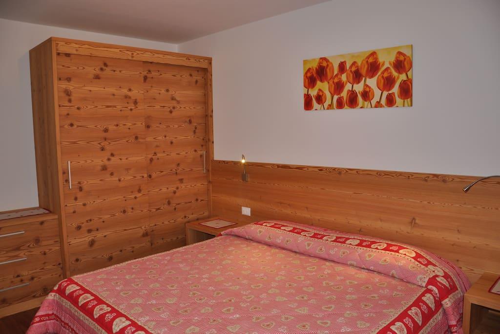 Ampia camera da letto arredata interamente in legno