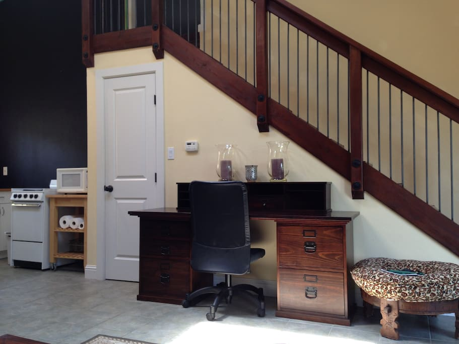 Stairs lead to the upstairs sleeping loft. A desk for working.