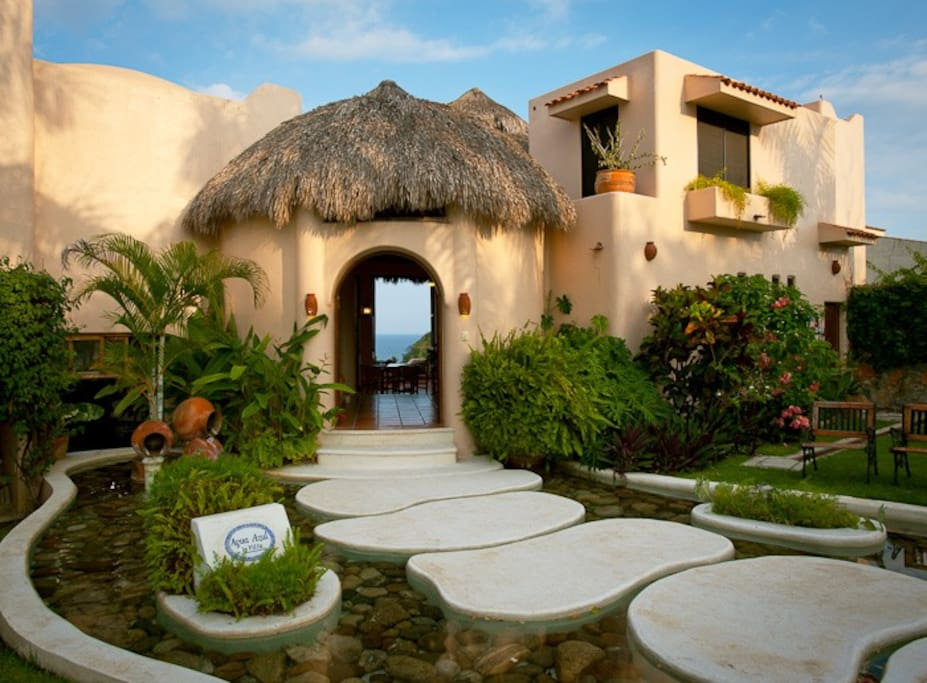 Enter the villa over five stepping stones set into a water feature