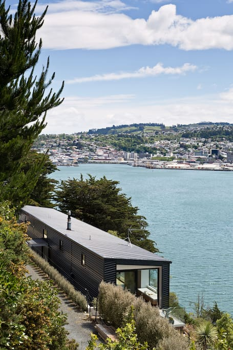 the house set on a steep bank above the harbour with vehicle access from behind