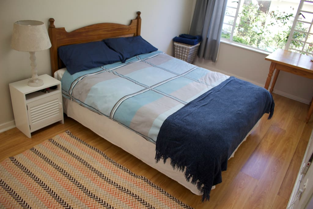 large room with queen size bed, desk and big built in cupboards