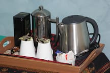 A room tray with kettle, coffee and plunger, chocolate, tea bags and biscuits.