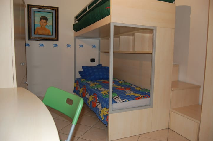 Kids' room with bunk beds, desk and wardrobe