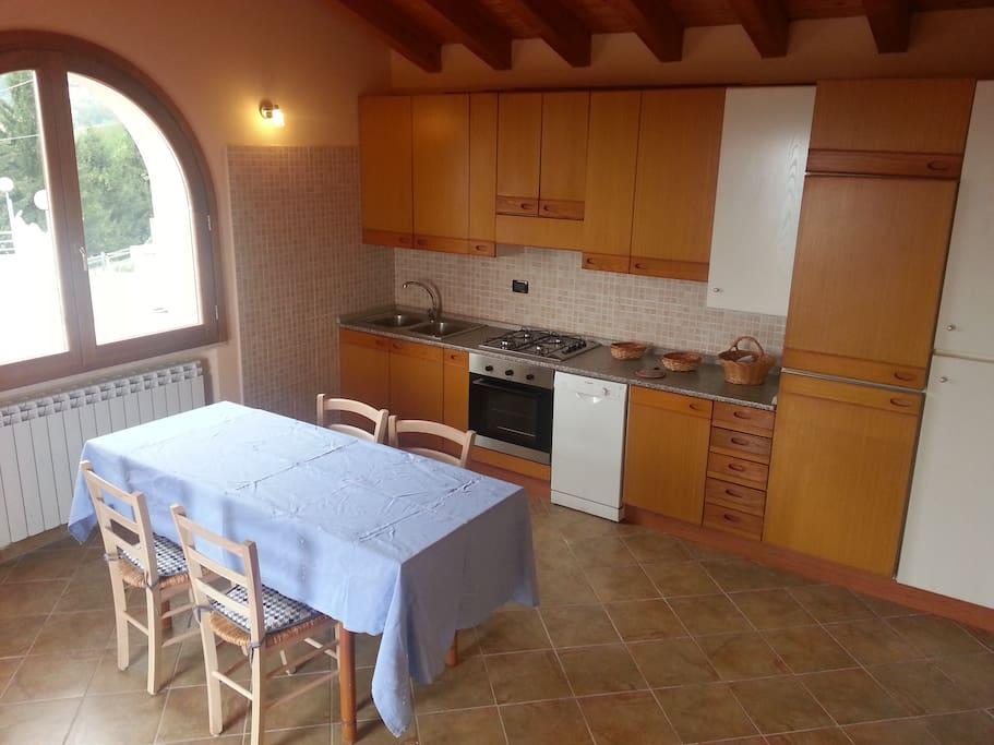 La cucina (con forno e lavastoviglie) e l'ampio salotto / The kitchen (with oven and dishwasher) and the wide living room