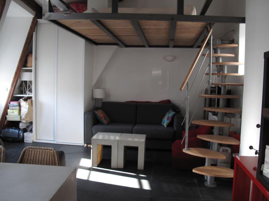 Salon avec canapé-lit deux places et accès à la mezzanine.
