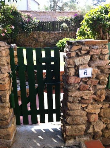 Il cancello di ingresso della casa, in legno, immette direttamente nel giardino privato della casa