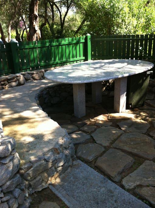 il tavolo da pranzo del giardino, con la panchina di pietra, può ospitare fino a 10 persone