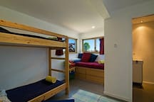 Bunk beds and a single bed with private tv and attached bathroom