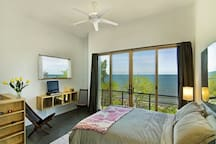 Queen sized bed with attached bathroom with large sliding glass door to allow lake breezes