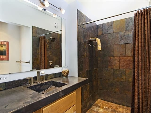 Bathroom with concrete counters and a slate shower