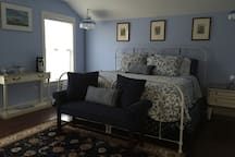 Bright sunny bedroom with king size bed