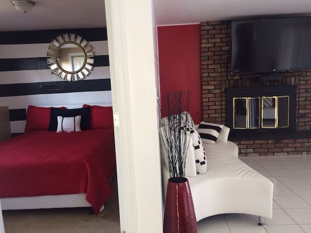 Modern decor one bedroom with queen size bed; living room with fireplace and large screen cable tv