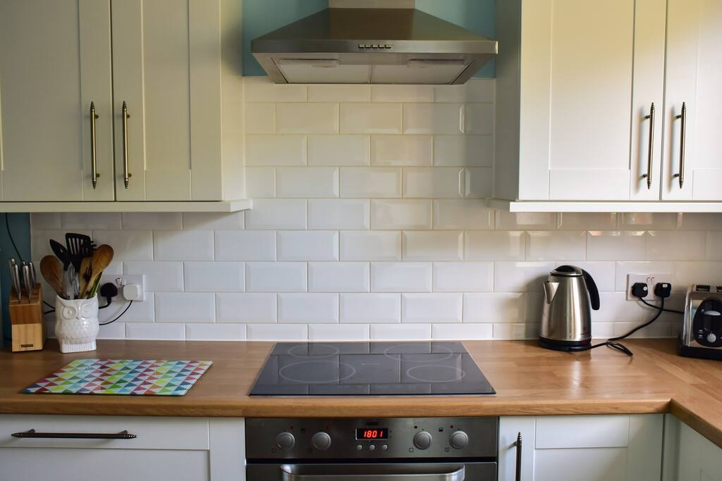 The kitchen offers induction hob, fan oven, dishwasher, washer/dryer, microwave oven and a dining area