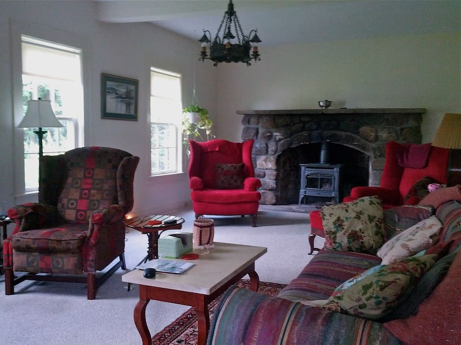 Spacious living room with gas stove fireplace, table for eating.