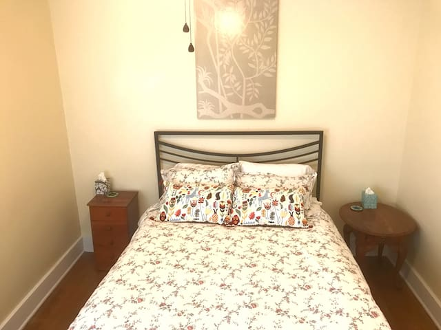 The second bedroom with a queen bed and sound machine