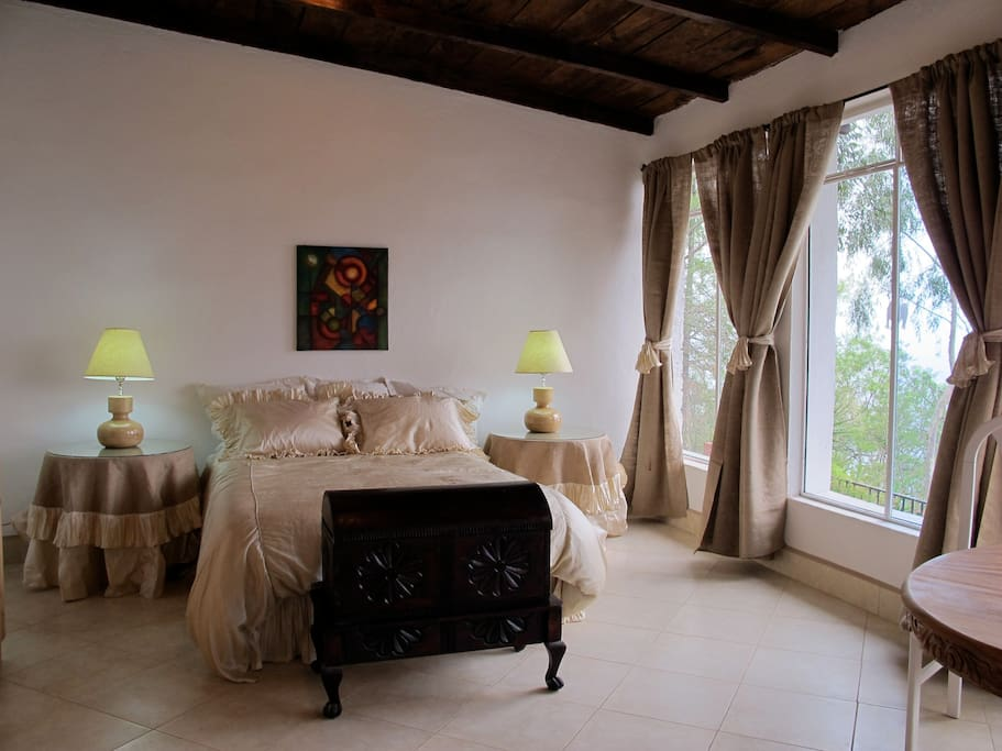 A spacious master bedroom with queen bed that has a private marble bath.