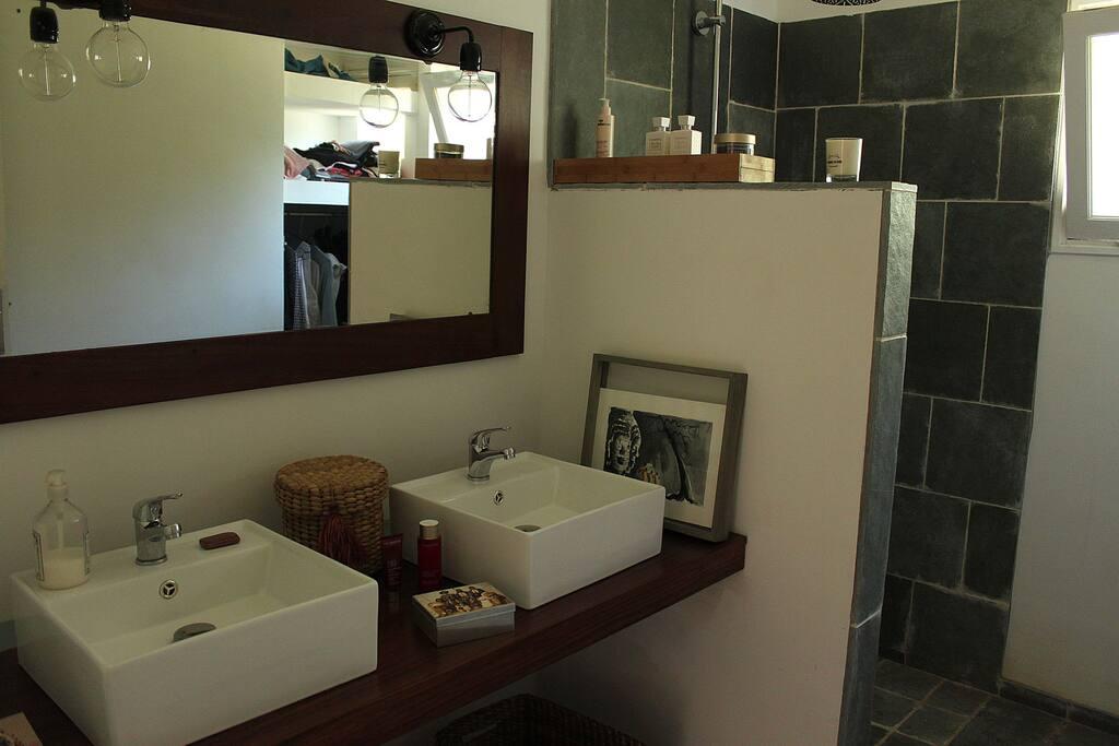Dans une pièce attenante, la salle d'eau, moderne et fonctionnelle avec une douche à l'italienne en pierre naturelle.