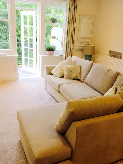 Lounge with sofa bed and doors out onto balcony overlooking Alum Chine