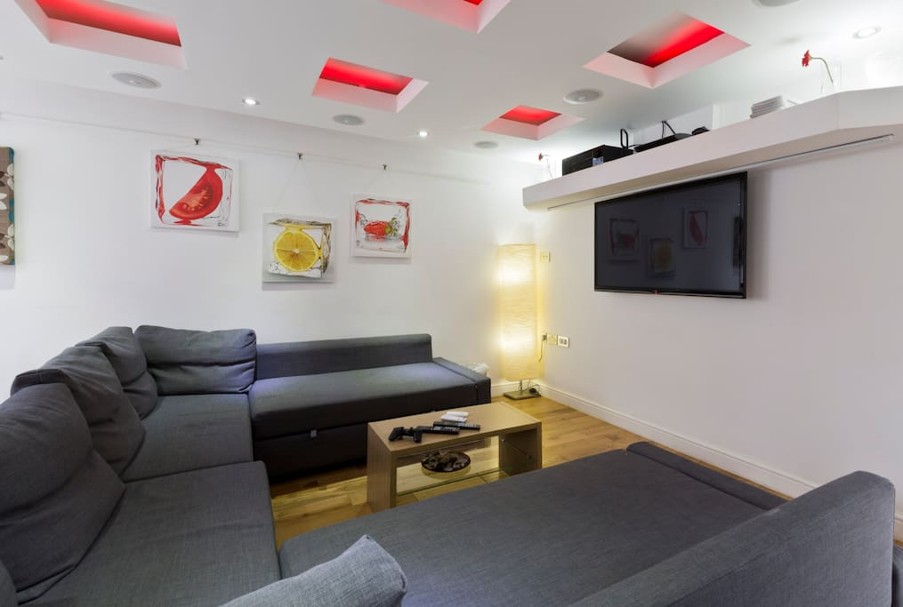 Reception Room - Home cinema with projector, screen, ceiling-mounted surround sound, light raft, widescreen TV, ample seating, dining table & 6 chairs