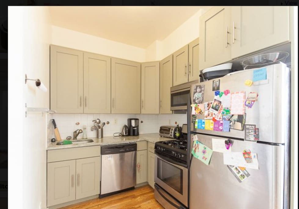 Kitchen filled with appliances. Refrigerator, dishwasher, microwave, oven, coffeemaker, blender, rice cooker, knives, and more