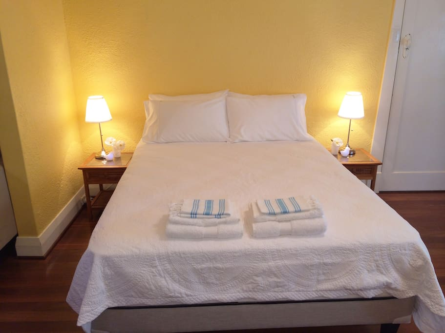 Queen size bed with lovely fresh bed linen and towels