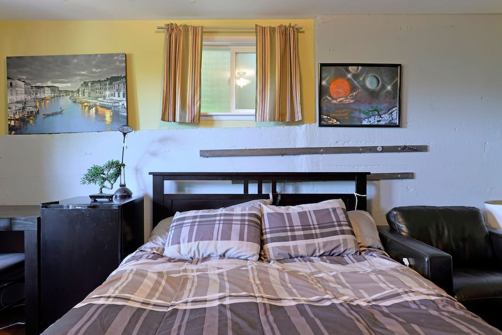 Bedroom with decorative art on cement walls, frosted glass window faces south
