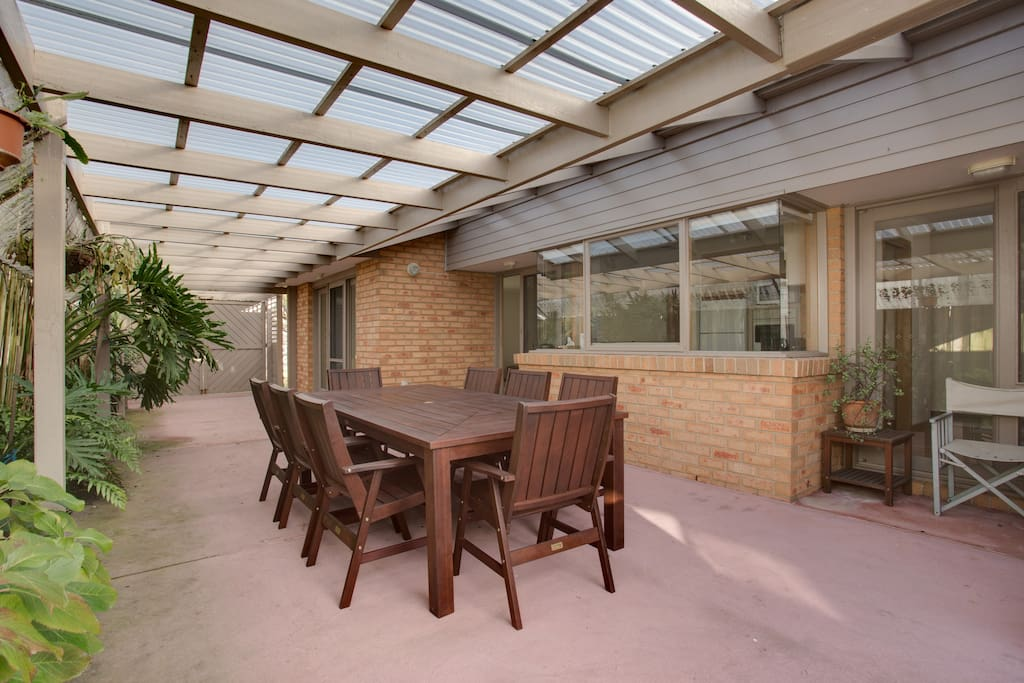 Large outdoor dining space lined with lush green foliage with room for further fold out tables , excellent bbq facilities and direct access to kitchen, indoor dining and large backyard