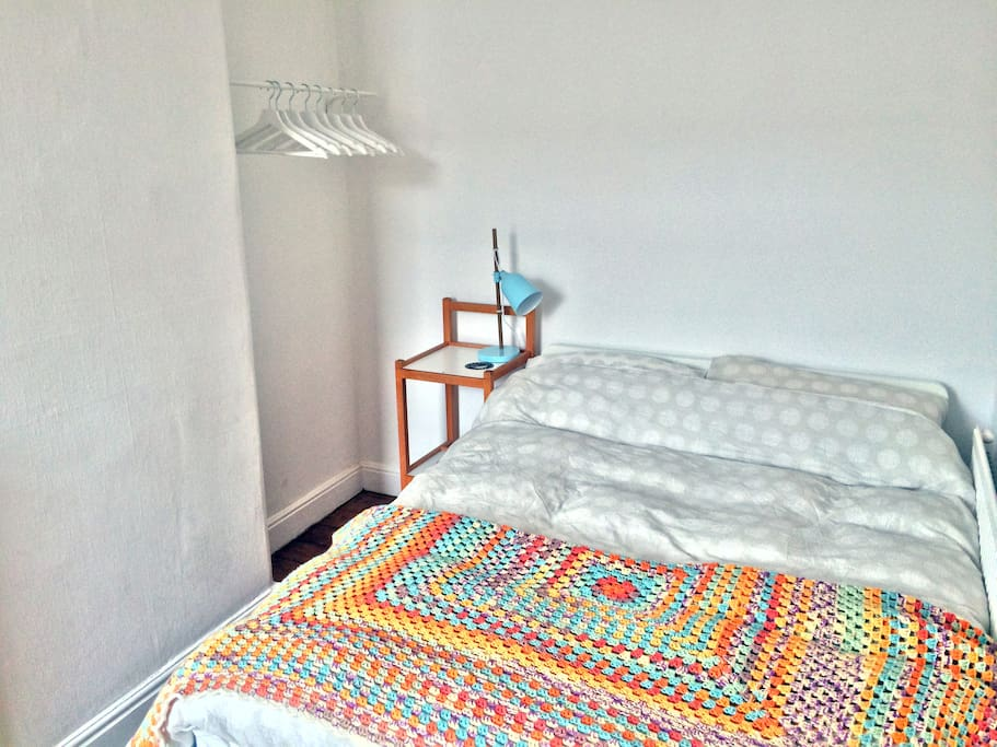 Guest bedroom - comfy bed, handy clothes rail, and side table and lamp with conveniently located power supply for your phone