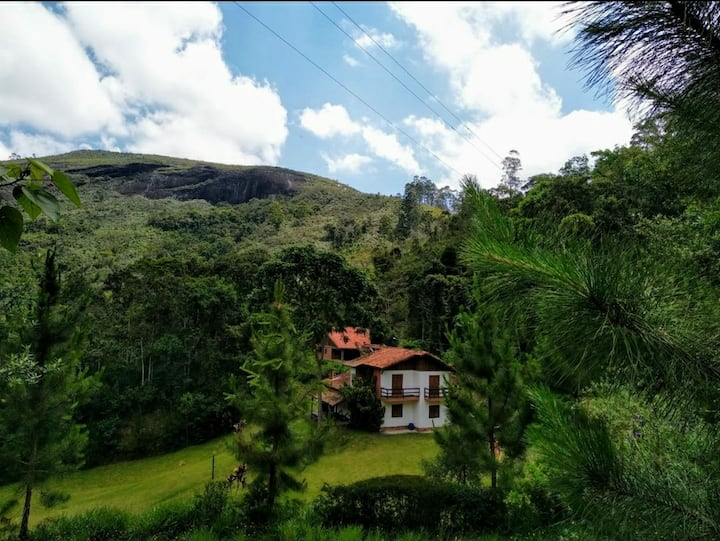 Bela casa de Campo cercada de flores e pinheiros.