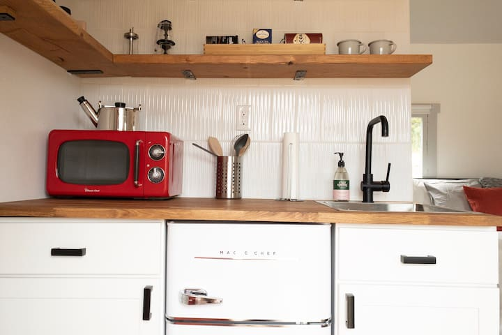 The tiny kitchen is equipped with a fridge, microwave, sink, induction cooktop, utensils and dishware.