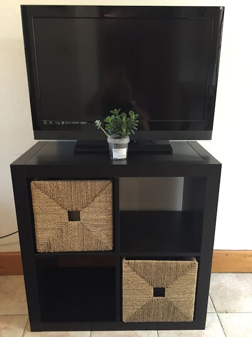 IKEA cube with storage drawers hosting a flat screen