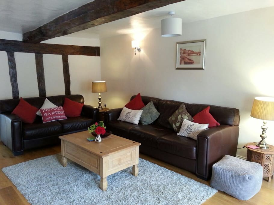 Beamed ceiling and inglenook fireplace with woodburner