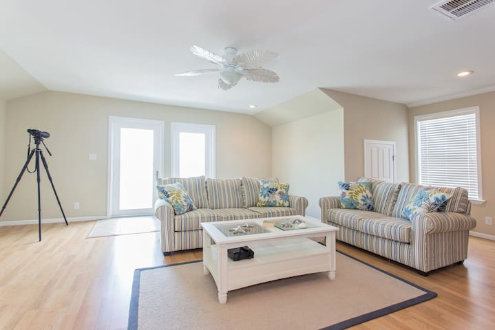 Family Room - Mostly Private - This room comes equipped with an enormous flat screen mounted on the wall, a full sized couch, a love seat, a U-Shaped desk, a full sized refrigerator, and a wonderful view.