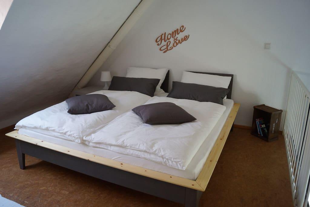 Galerie-Schlafzimmer mit Doppelbett (1.80x2 m) und einem Schrank sowie TV