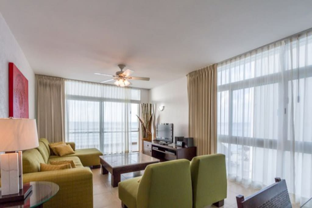 Living room has comfortable couches, cable TV and access the oceanfront balcony